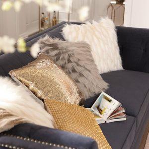 Neutral and metallic pillows layered on navy sofa